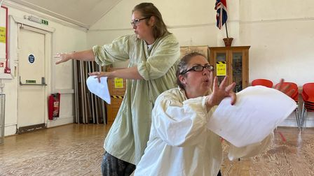Two women rehearse for a play in a small hall.