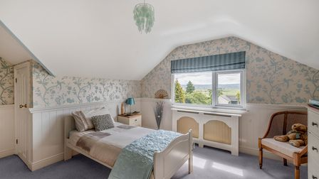 stylish bedroom with half white and light blue patterned wallpaper, half white wood-panelled walls, vaulted ceiling