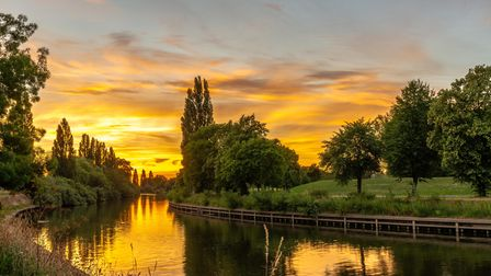 A dramatic sunset over a bend in the River Ouse in York. A path runs alongside a tree-lined river b