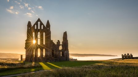 The Gothic ruins of Whitby Abbey with the suns rays producing a star. Sea mist held back by the cli