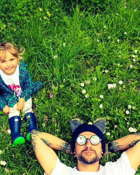 A man and his son lying in the grass.