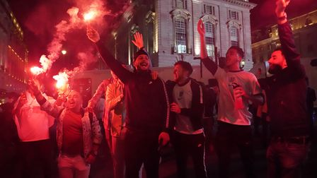 Fans let of flares as they celebrate in Piccadilly Circus, central London after England qualified fo