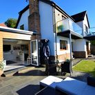 back of a large house with balconies and extension with bi-folding doors onto a patio and lawn