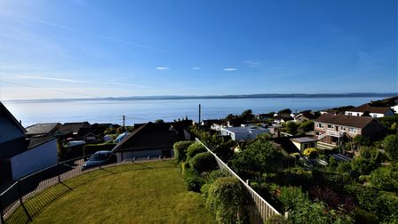 garden and properties behind and on the right and sea in the background and Welsh coastline beyond