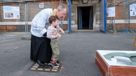 Father Walker with his grandson Raphael at the ceremony blessing the new weathervane at St Jude's
