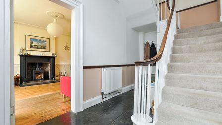 hallway with black tiled floor, white and coffee walls, white doorway to sitting room, staircase on right with beige carpet