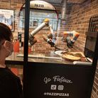 PARIS, FRANCE - JULY 09: A woman watches as her pizza is prepared at Pazzi, Paris' first robotic piz
