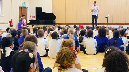 Into Opera choral director Patrick Barrett with pupils atSt Francis of Assisi Catholic Primary School.