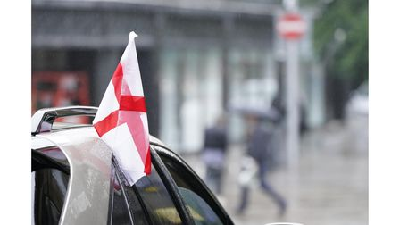 An England flag hanging from a car the morning after England were beaten in the