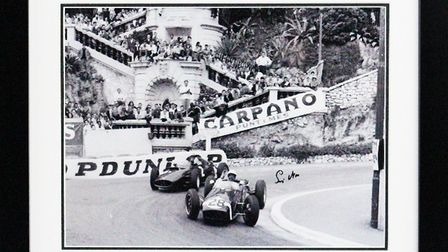 Ablack and white photo of Sir Stirling Moss in action at Monaco, signed by the sporting legend