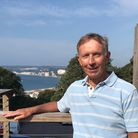 Brian Thompson on the balcony outside the clubhouse overlooking Seaton Beach & Bay