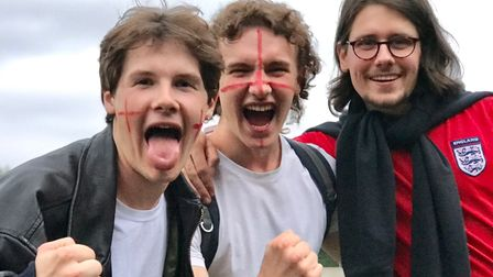 Three England fans happy. Two have their faces painted with the St George's Cross and roar!
