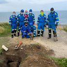 Sheringham and Cromer Coastguard with a dog which they rescued from a buried pillbox on the North Norfolk coast