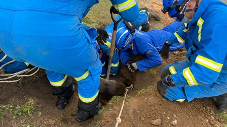 Cromer and Sheringham Coastguard rescuing Toby the cocker spaniel from a buried pillbox on the North Norfolk coast.