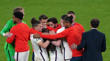 England's Bukayo Saka is consoled by manager Gareth Southgate and team mates after missing during th