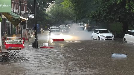 A vehicle starts to smoke amid floods in South End Green