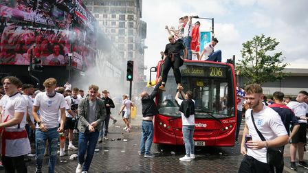 England fans climb aboard a bus outside the ground ahead of the UEFA Euro 2020 Final at Wembley Stad