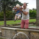 David Church with his grandson Henry Church enjoying the fountains at Waterloo Park in Norwich. Pict