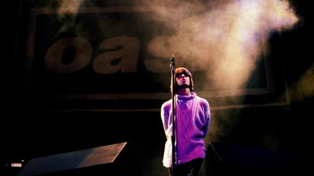 Photo of Liam Gallagher performing live onstage, with Oasis logo behind him.