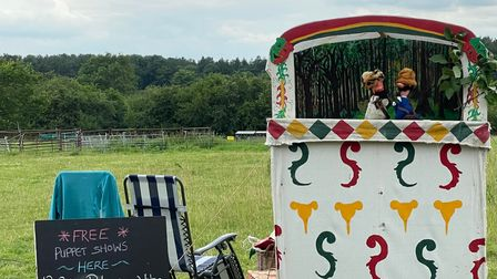 A puppet theatre booth in a field outside.