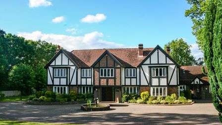 A modern, Tudor-style house surrounded by trees, shrubs and a small drive with a fountain