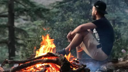 A man rests beside a roaring fire in the woods