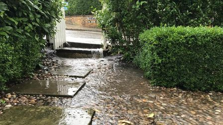 Water streams into the front garden of a home in Keats Grove