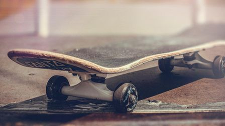 A close up of a skateboard stationary at the top of a ramp.