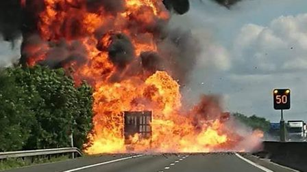 Flames on the M11 motorway. A lorry on fire is obscured by plumes of yellow flames.