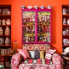 Club sofa upholstered in kilim material beneath glass-fronted pink cabinet.