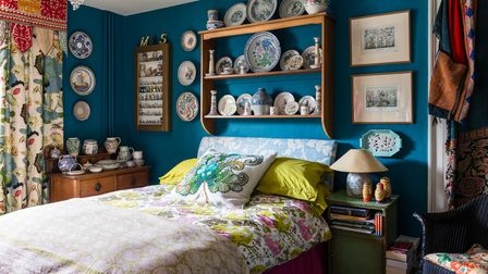 Poole pottery displayed on wooden shelf in bedroom painted in Deep Space Blue.
