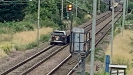 A mobile phone image of a car driving on railway tracks