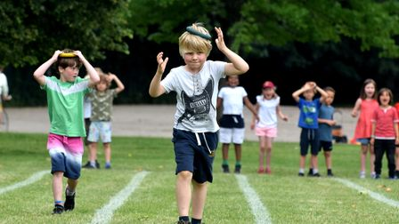 Pupilscompete in a relay race while balancing a quoit on their head
