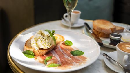 A plate of eggs benedict on toast with Parma ham. A glass of prosecco sits next to the plate
