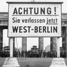 Guards at stand at the Brandenburg Gate, as the Berlin Wall goes up behind them, in August 1961