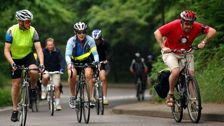 Cyclists in the early stage of the 50/100 mile bike ride, tackling the hills on Mousehold Heath that