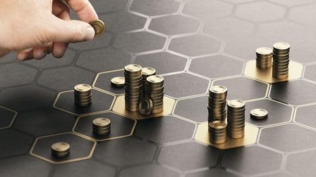 Human hand stacking generic coins over a black background with hexagonal golden shapes. Concept of i
