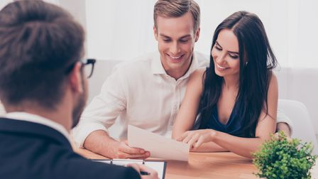 Successful lawyer giving consultation to family couple about buying house