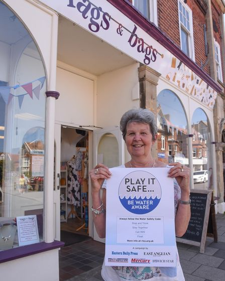 Moya Roseby, owner of Rags & Bags in Sheringham, with the water safety campaign poster. Picture: Dan