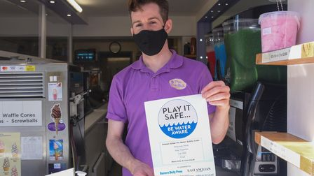 Jack Button, owner of the Ice Hut in Sheringham, with a water safety campaign poster. Picture: Danie