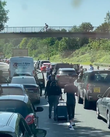 A queue of cars on the M11. In the centre: two people carry suitcases along the centre of the road
