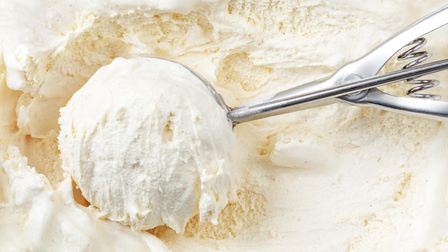 Vanilla ice cream with a scoop in container as background. Macro. Scooped out ice-cream, top view.