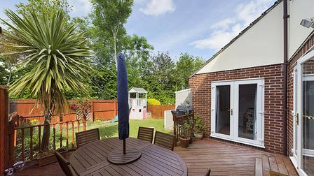 The rear garden with decking and a lawn