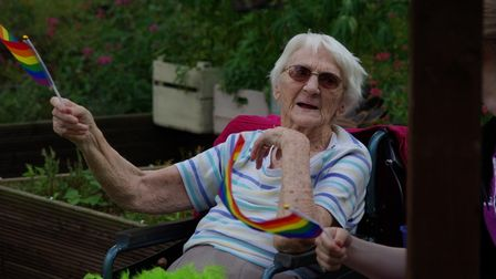 Care Home resident Lorna flying flag forLGBTQ+ Pride