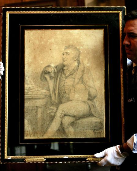 A Sotherby's technician shows off a portrait of Samuel Taylor Coleridge, signed and dated G. Dawe 1812