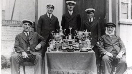 An old crew for the Maidie surrounded by trophies.