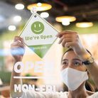Business owner Asian woman wear protective face mask ppe hanging open sign at her restaurant / café