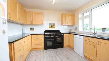 three-sided kitchen with light wood cupboards, black range cooker, white dishwasher, black worktops and a window on the right