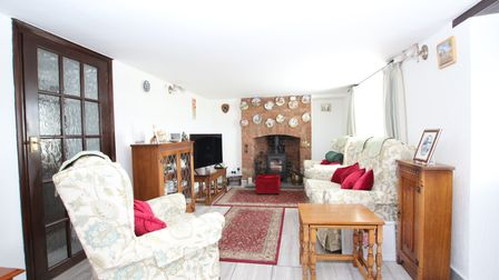 sitting room with white walls, stone surrounded open fireplace with wood burner, white patterned sofa and chair