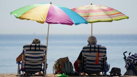 People sit under umbrallas as they enjoy the hot weather at Bournemouth Beach in Dorset. Picture dat